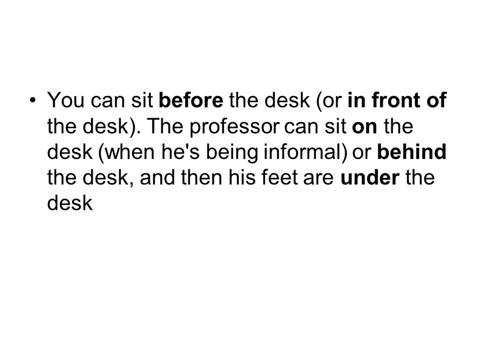 You can sit before the desk (or in front of the desk)