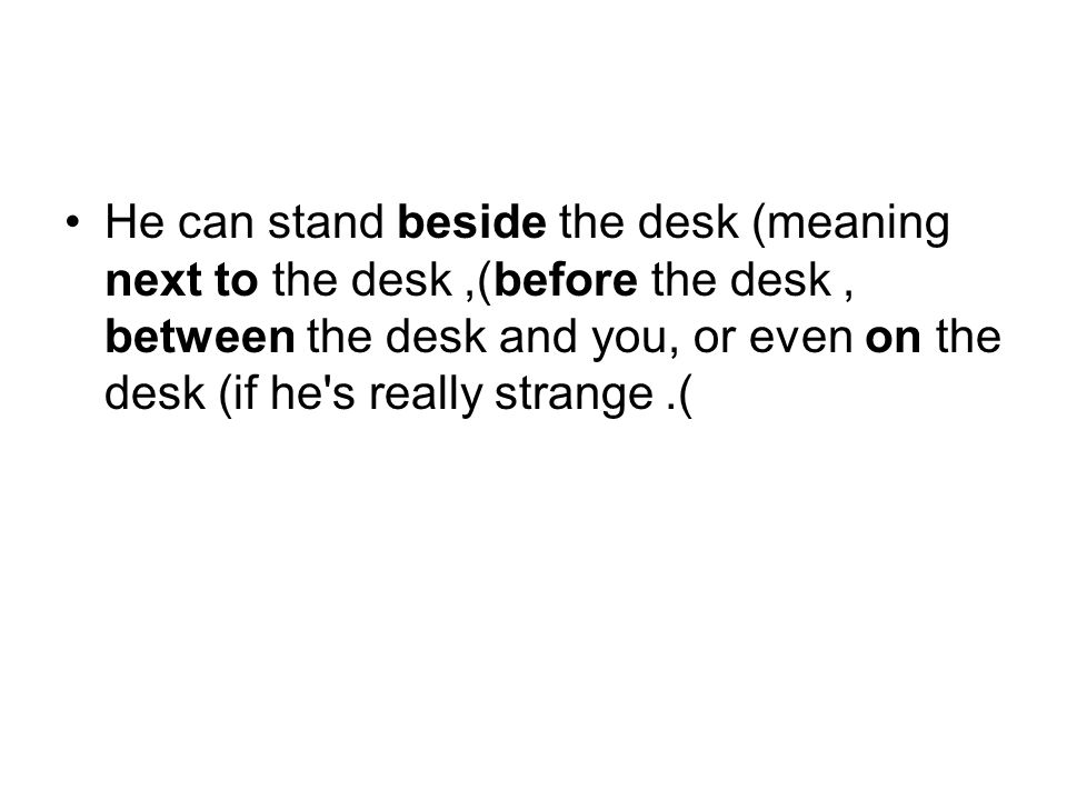 He can stand beside the desk (meaning next to the desk), before the desk, between the desk and you, or even on the desk (if he s really strange).