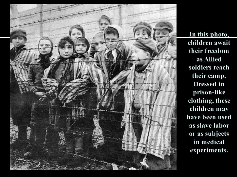 In this photo, children await their freedom as Allied soldiers reach their camp.