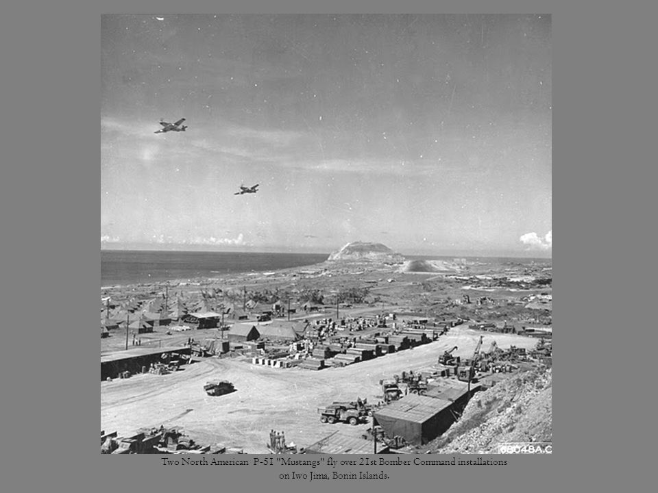 Two North American P-51 Mustangs fly over 21st Bomber Command installations on Iwo Jima, Bonin Islands.