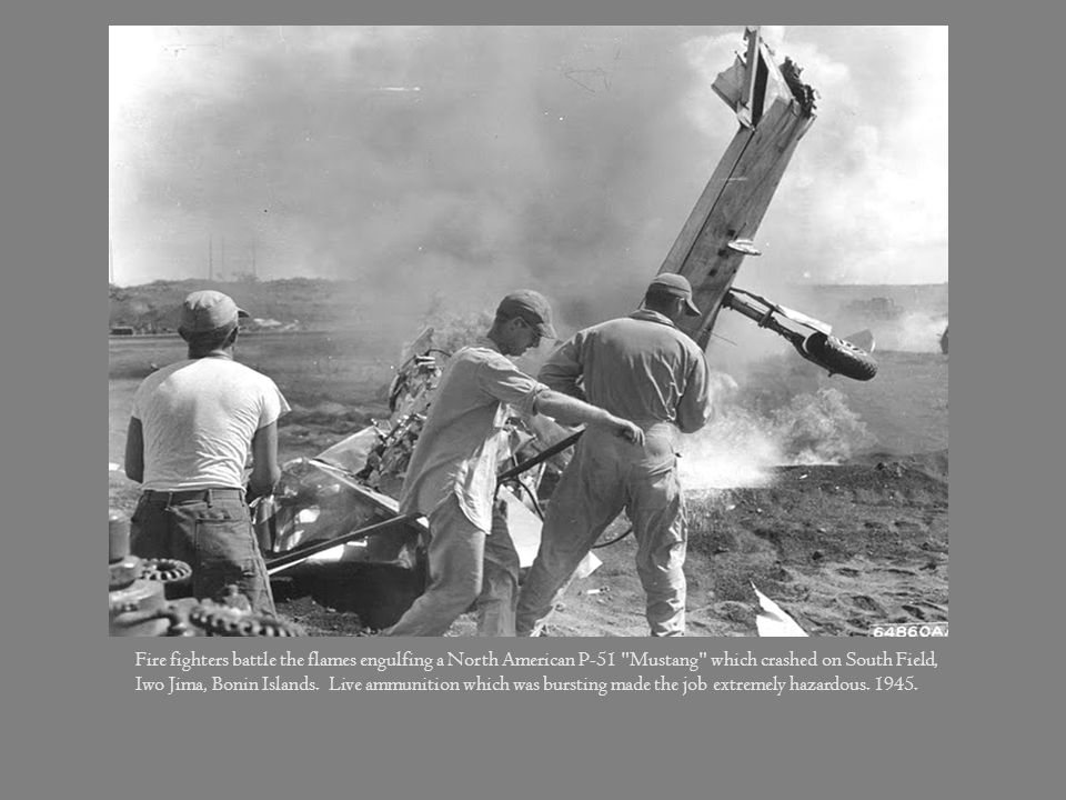 Fire fighters battle the flames engulfing a North American P-51 Mustang which crashed on South Field, Iwo Jima, Bonin Islands. Live ammunition which was bursting made the job extremely hazardous.