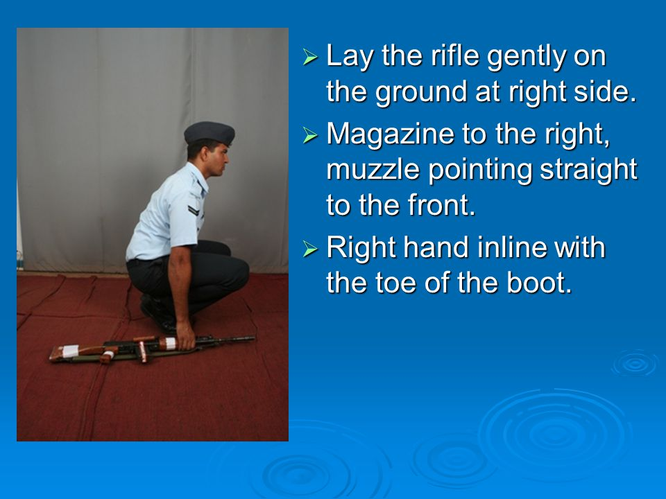 Lay the rifle gently on the ground at right side.