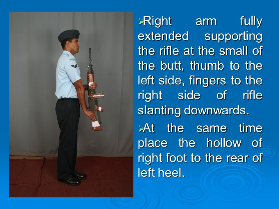 Right arm fully extended supporting the rifle at the small of the butt, thumb to the left side, fingers to the right side of rifle slanting downwards.