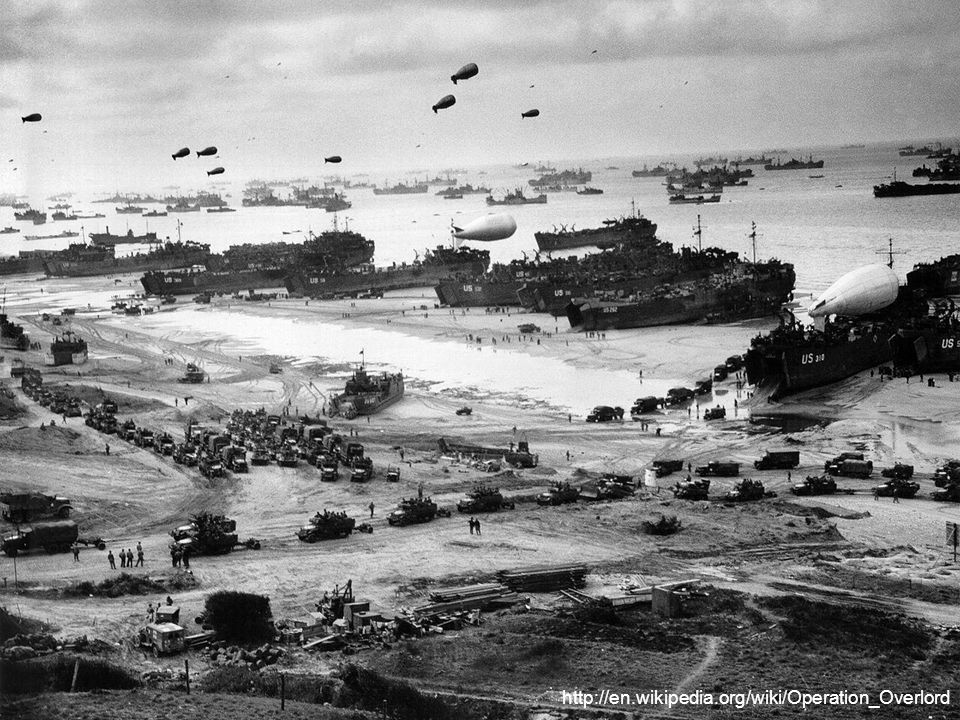 Landing ships putting cargo ashore on Omaha Beach, at low tide during the first days of the operation, mid-June, 1944.