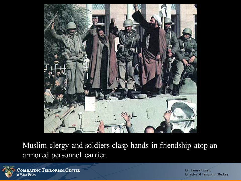 Muslim clergy and soldiers clasp hands in friendship atop an armored personnel carrier.