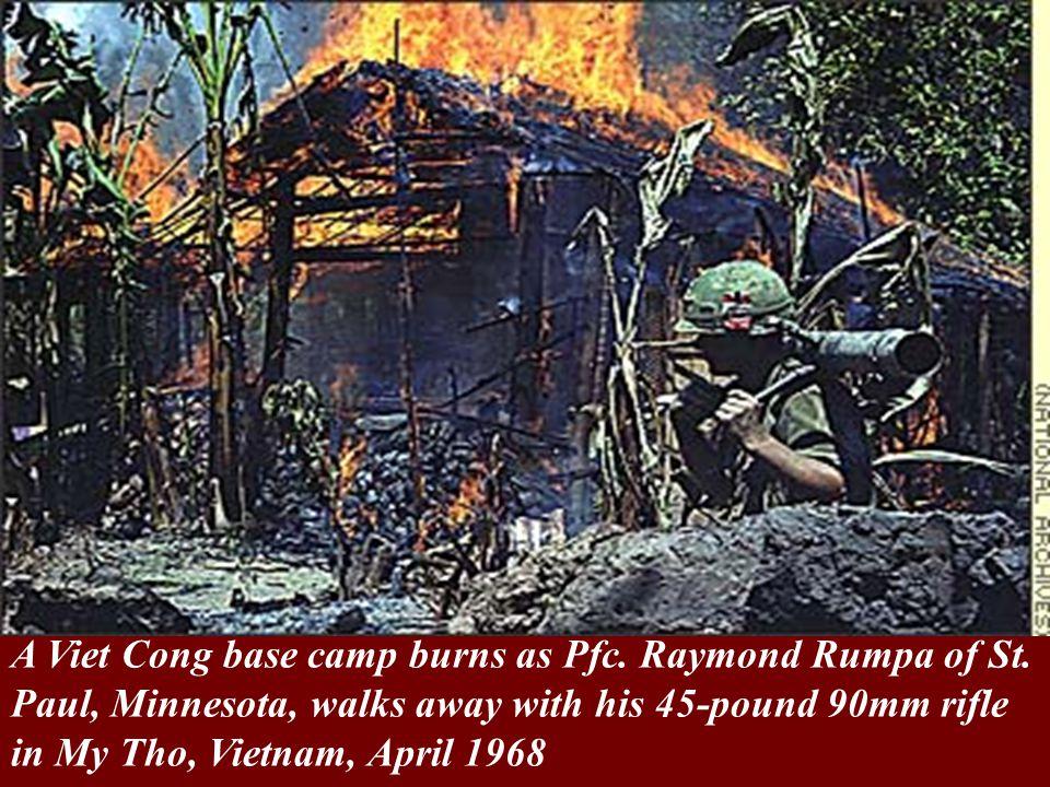 A Viet Cong base camp burns as Pfc. Raymond Rumpa of St