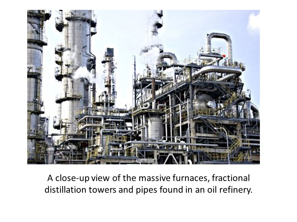 A close-up view of the massive furnaces, fractional distillation towers and pipes found in an oil refinery.