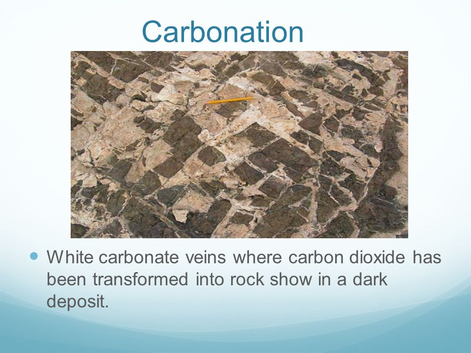 Carbonation White carbonate veins where carbon dioxide has been transformed into rock show in a dark deposit.