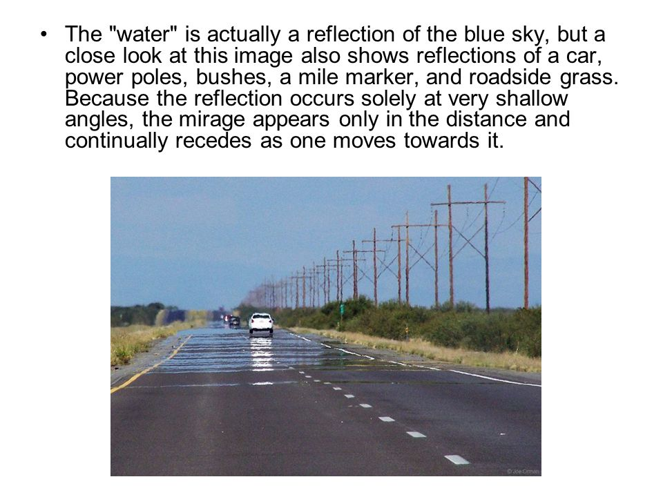 The water is actually a reflection of the blue sky, but a close look at this image also shows reflections of a car, power poles, bushes, a mile marker, and roadside grass.
