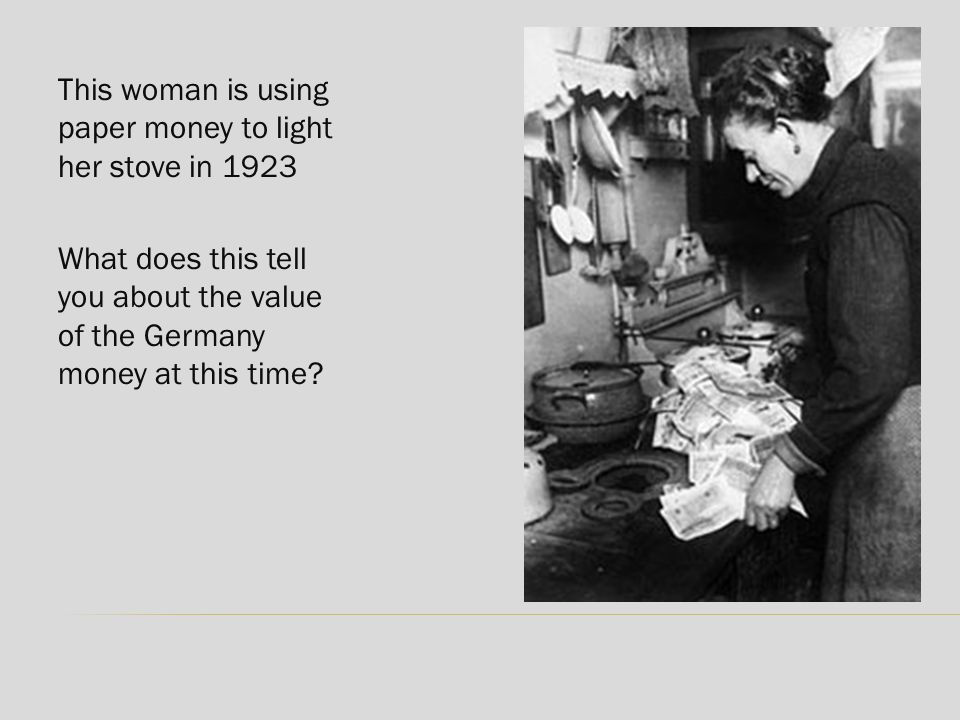 This woman is using paper money to light her stove in 1923