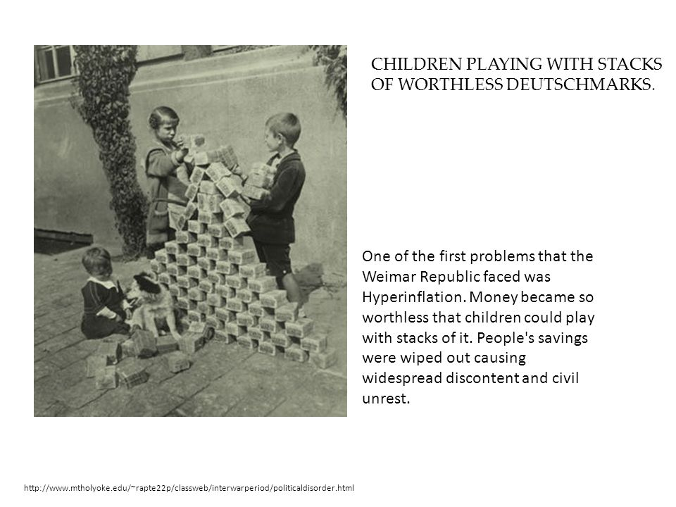 CHILDREN PLAYING WITH STACKS OF WORTHLESS DEUTSCHMARKS.