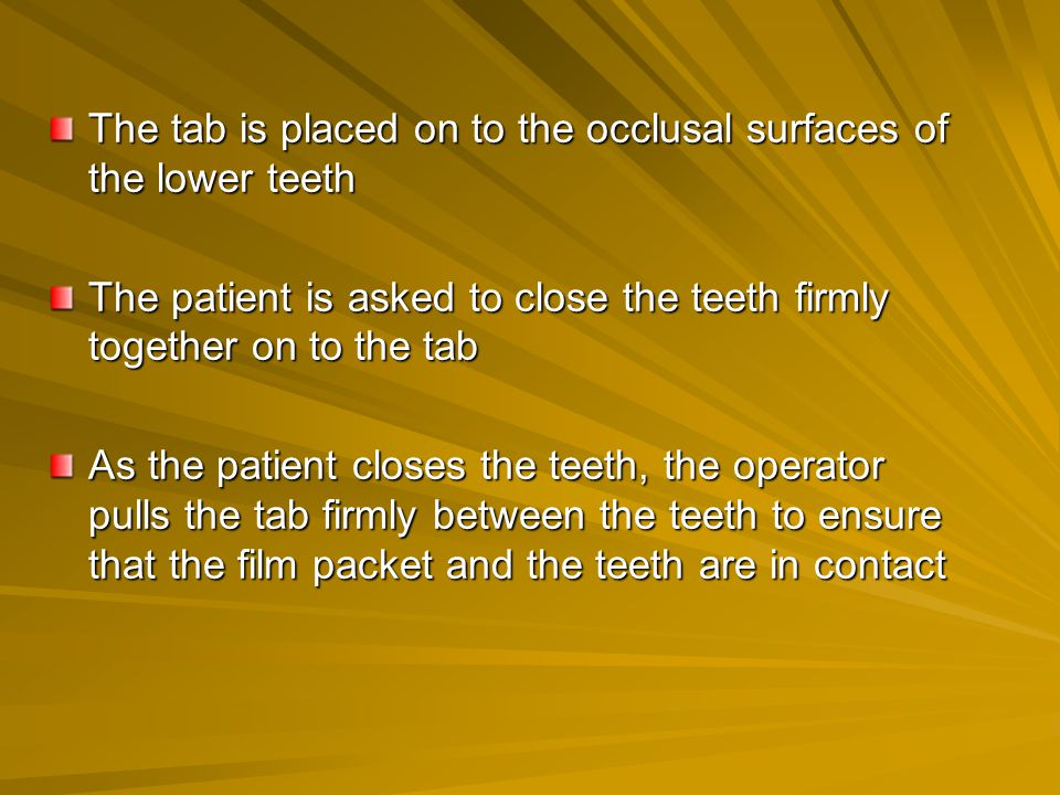The tab is placed on to the occlusal surfaces of the lower teeth