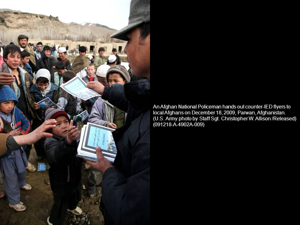 An Afghan National Policeman hands out counter-IED flyers to local Afghans on December 18, 2009, Parwan, Afghanistan.
