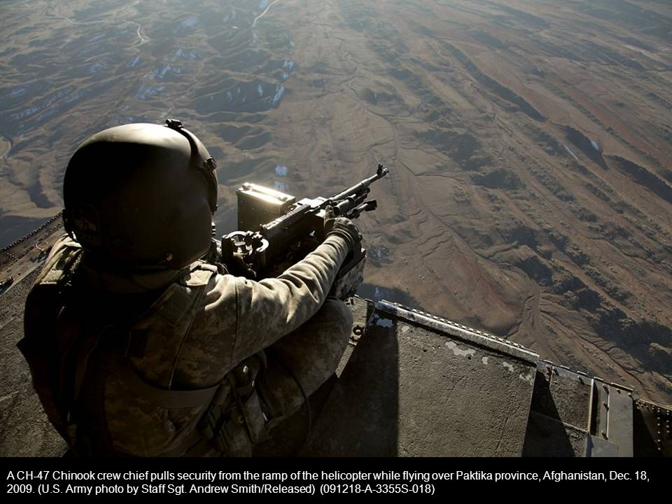 A CH-47 Chinook crew chief pulls security from the ramp of the helicopter while flying over Paktika province, Afghanistan, Dec.
