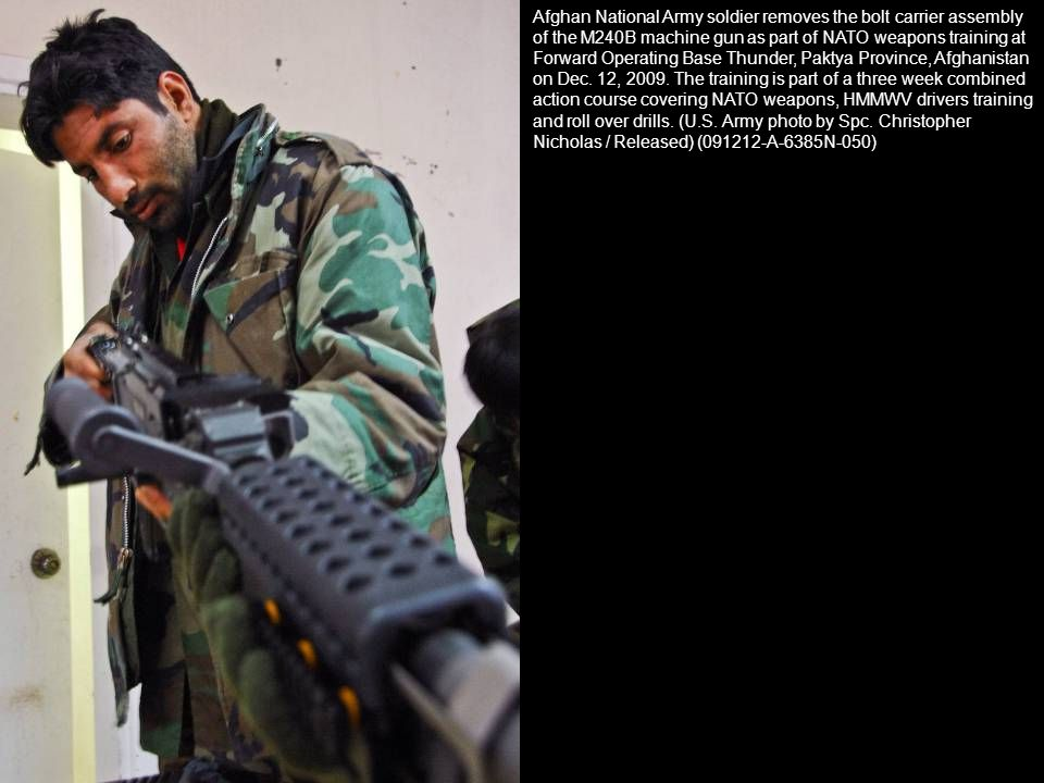 Afghan National Army soldier removes the bolt carrier assembly of the M240B machine gun as part of NATO weapons training at Forward Operating Base Thunder, Paktya Province, Afghanistan on Dec.