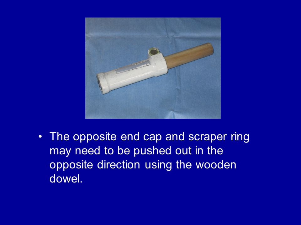 The opposite end cap and scraper ring may need to be pushed out in the opposite direction using the wooden dowel.