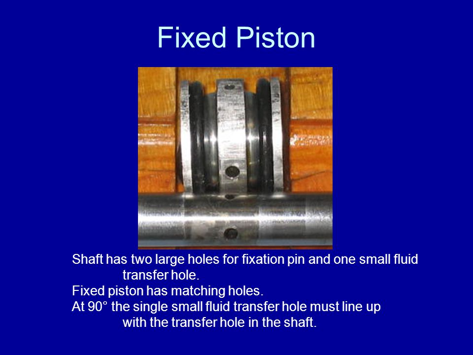 Fixed Piston Shaft has two large holes for fixation pin and one small fluid transfer hole. Fixed piston has matching holes.