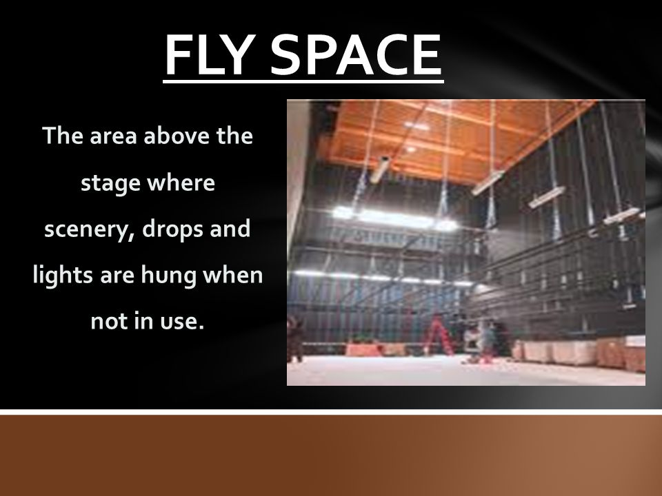 FLY SPACE The area above the stage where scenery, drops and lights are hung when not in use.