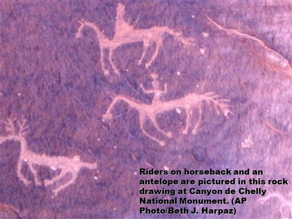 Riders on horseback and an antelope are pictured in this rock drawing at Canyon de Chelly National Monument.
