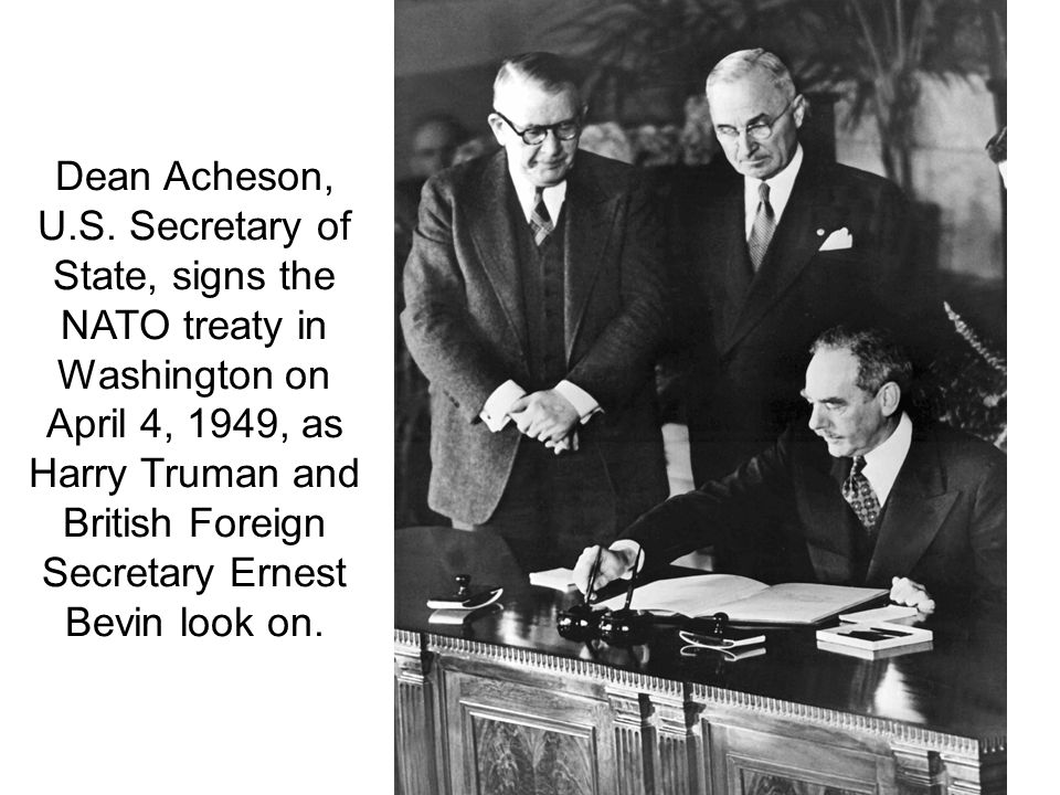 Dean Acheson, U.S. Secretary of State, signs the NATO treaty in Washington on April 4, 1949, as Harry Truman and British Foreign Secretary Ernest Bevin look on.