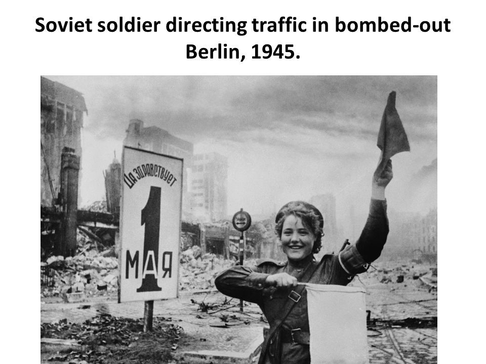Soviet soldier directing traffic in bombed-out Berlin, 1945.