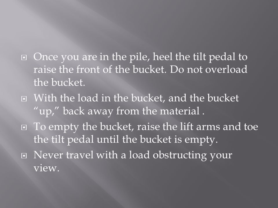 Once you are in the pile, heel the tilt pedal to raise the front of the bucket. Do not overload the bucket.