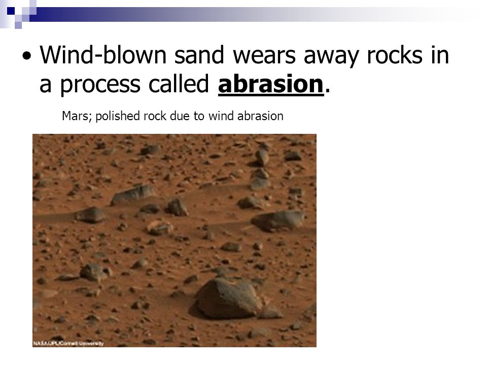 Wind-blown sand wears away rocks in a process called abrasion.