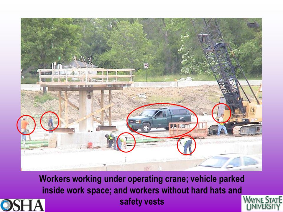 Workers working under operating crane; vehicle parked inside work space; and workers without hard hats and safety vests