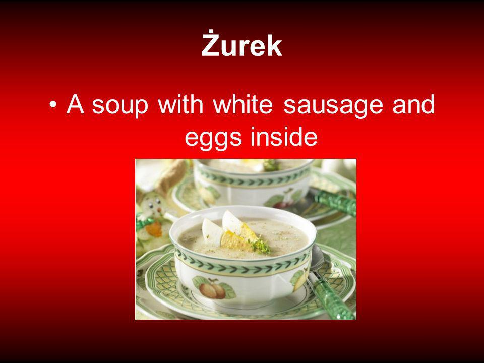 A soup with white sausage and eggs inside