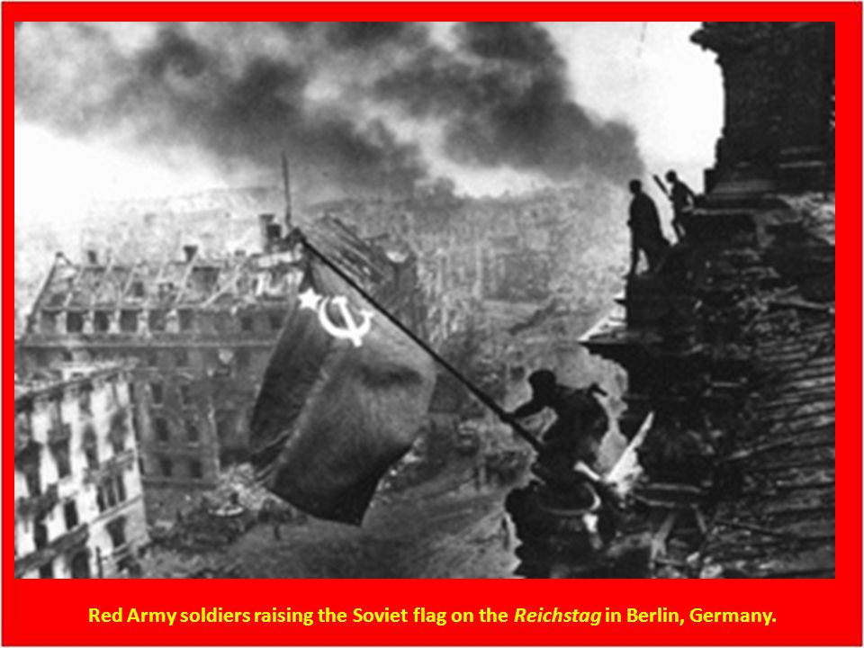 Red Army soldiers raising the Soviet flag on the Reichstag in Berlin, Germany.