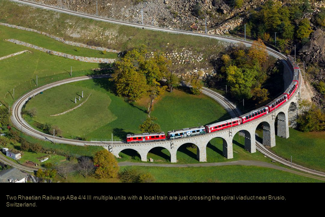 Two Rhaetian Railways ABe 4/4 III multiple units with a local train are just crossing the spiral viaduct near Brusio, Switzerland.