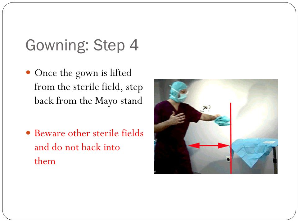 Gowning: Step 4 Once the gown is lifted from the sterile field, step back from the Mayo stand.