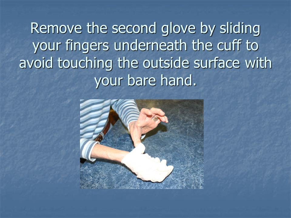 Remove the second glove by sliding your fingers underneath the cuff to avoid touching the outside surface with your bare hand.
