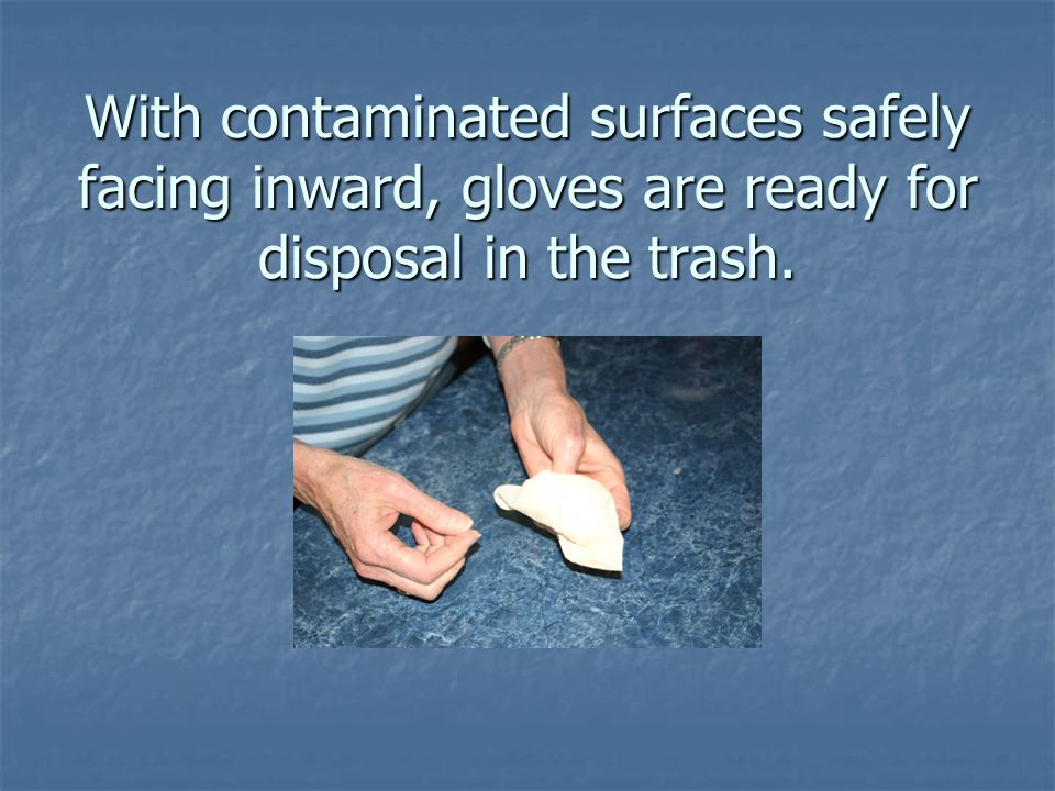 With contaminated surfaces safely facing inward, gloves are ready for disposal in the trash.