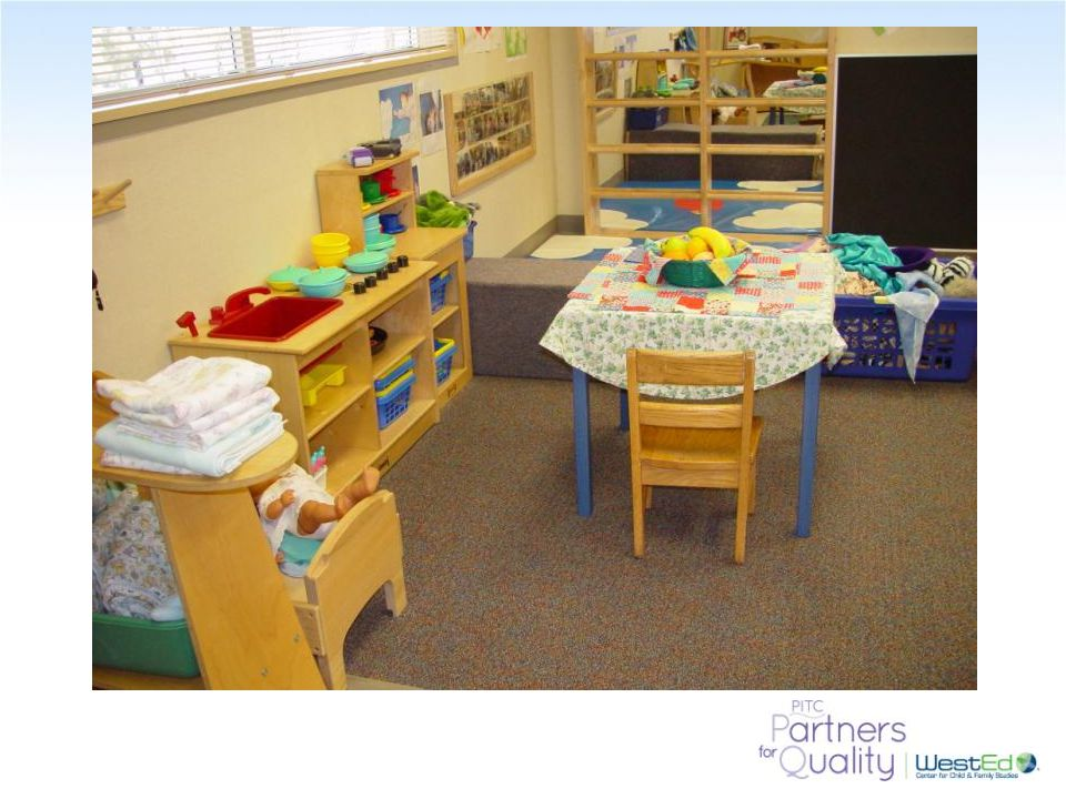 Notice the table cloth in the dramatic play area and the baby blankets on the table near the cradle.
