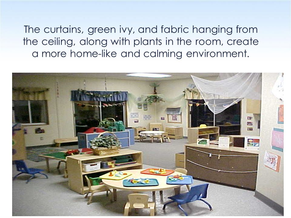 The curtains, green ivy, and fabric hanging from the ceiling, along with plants in the room, create a more home-like and calming environment.