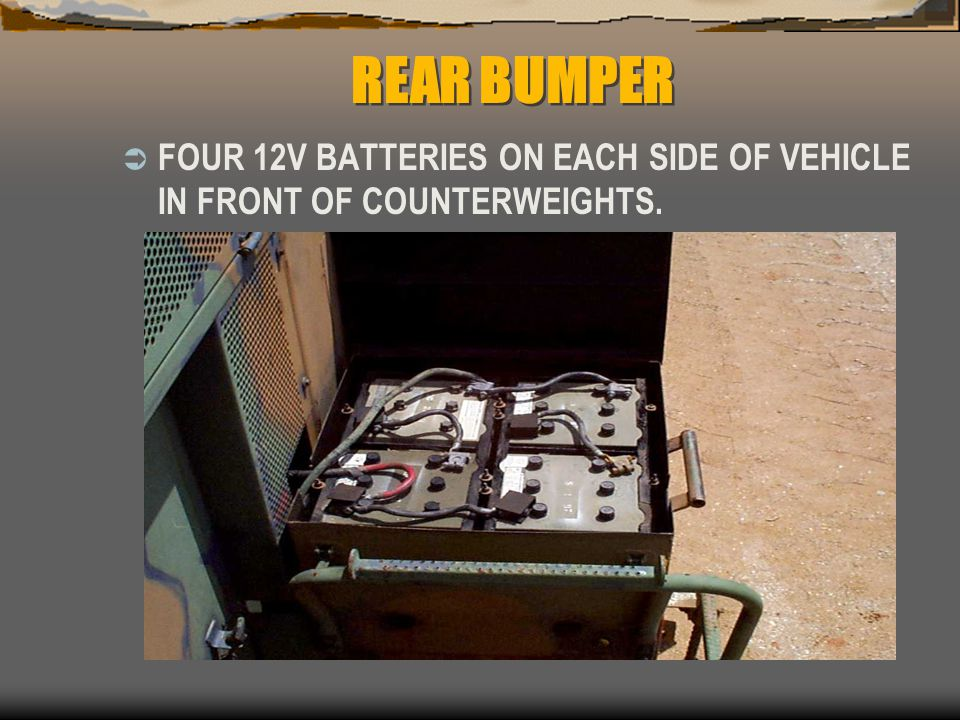 REAR BUMPER FOUR 12V BATTERIES ON EACH SIDE OF VEHICLE IN FRONT OF COUNTERWEIGHTS.