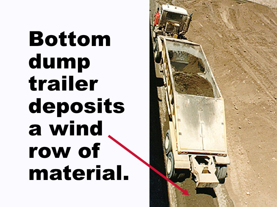 Bottom dump trailer deposits a wind row of material.
