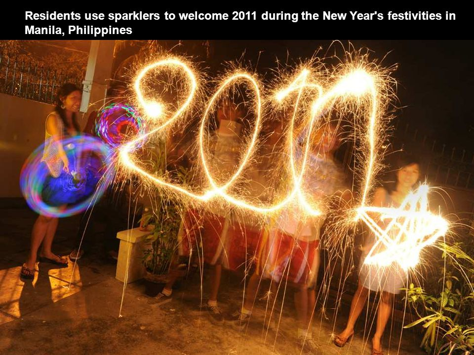 Residents use sparklers to welcome 2011 during the New Year s festivities in Manila, Philippines
