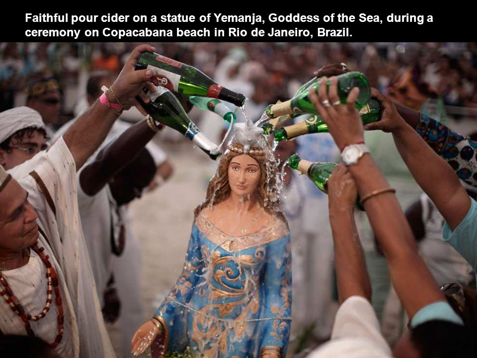 Faithful pour cider on a statue of Yemanja, Goddess of the Sea, during a ceremony on Copacabana beach in Rio de Janeiro, Brazil.