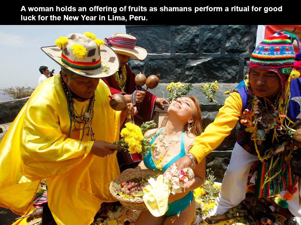A woman holds an offering of fruits as shamans perform a ritual for good luck for the New Year in Lima, Peru.