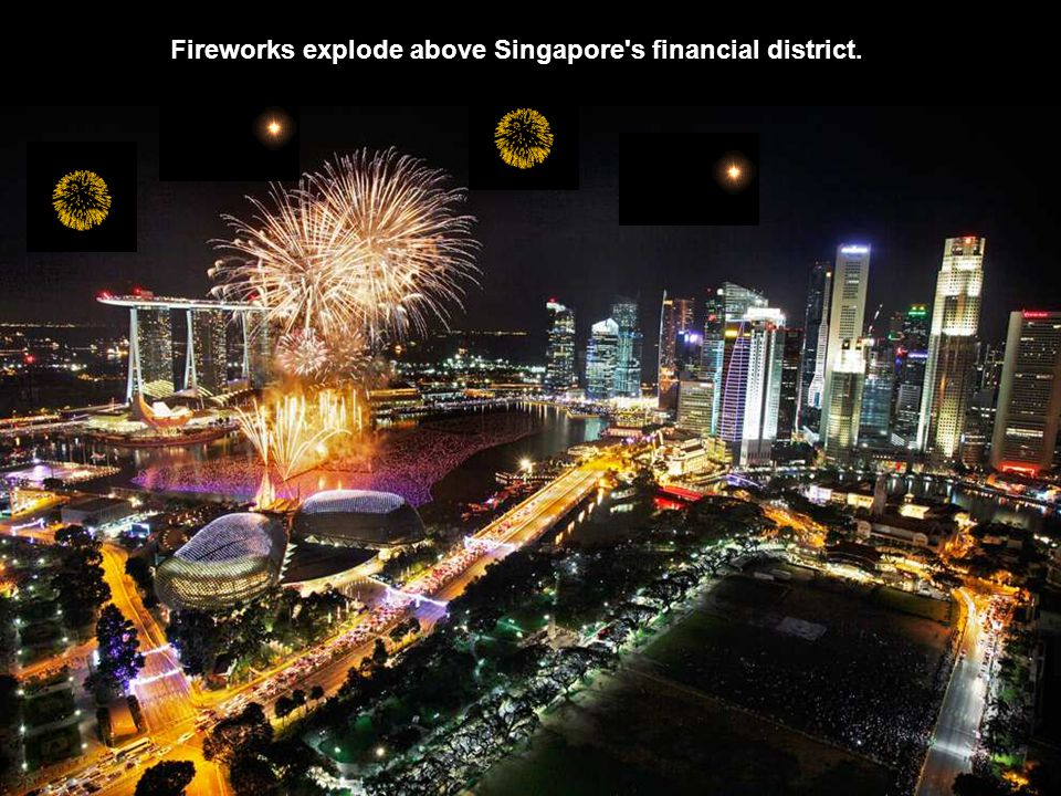 Fireworks explode above Singapore s financial district.