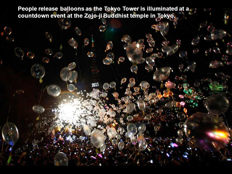 People release balloons as the Tokyo Tower is illuminated at a countdown event at the Zojo-ji Buddhist temple in Tokyo.