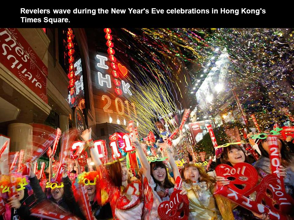 Revelers wave during the New Year s Eve celebrations in Hong Kong s Times Square.