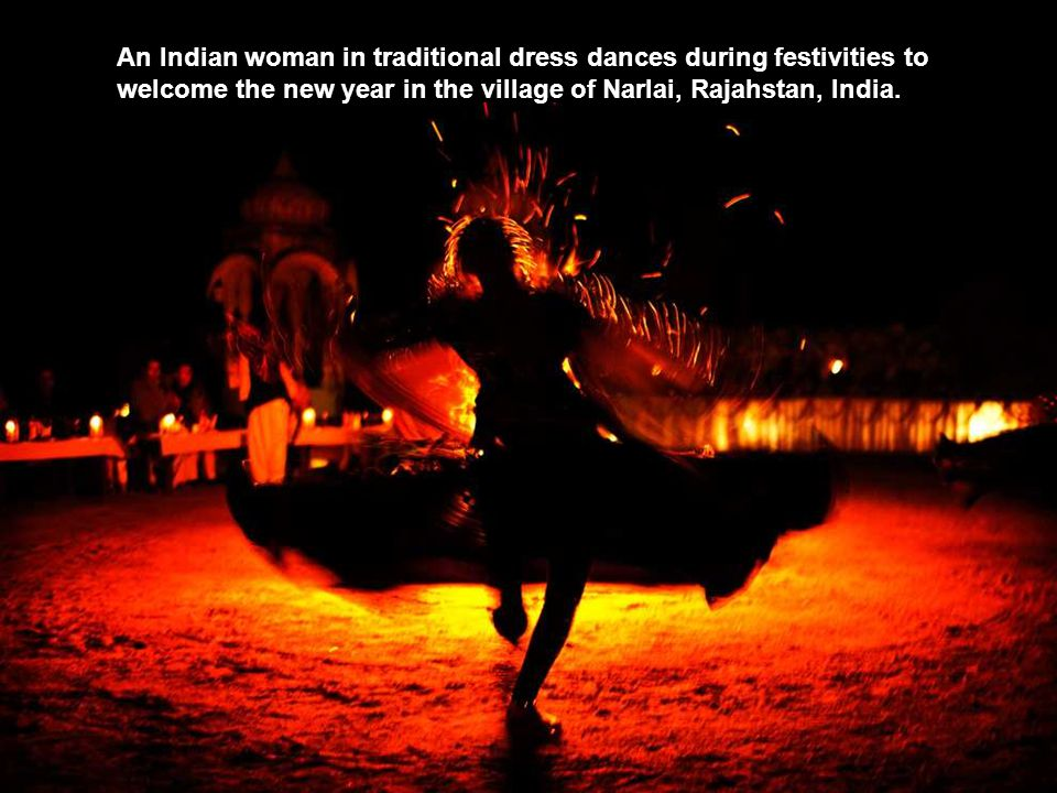 An Indian woman in traditional dress dances during festivities to welcome the new year in the village of Narlai, Rajahstan, India.