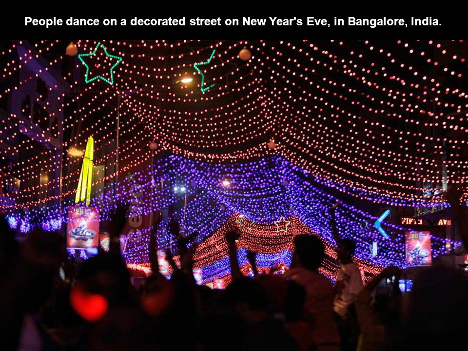 People dance on a decorated street on New Year s Eve, in Bangalore, India.