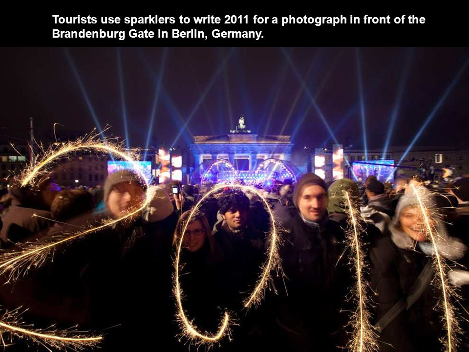 Tourists use sparklers to write 2011 for a photograph in front of the Brandenburg Gate in Berlin, Germany.