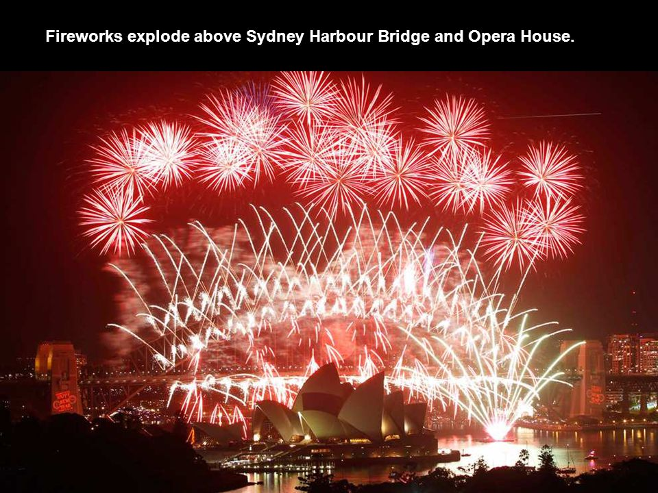 Fireworks explode above Sydney Harbour Bridge and Opera House.