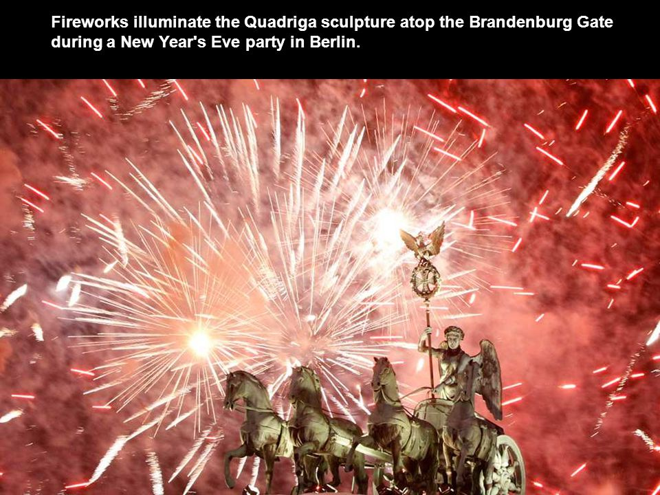 Fireworks illuminate the Quadriga sculpture atop the Brandenburg Gate during a New Year s Eve party in Berlin.