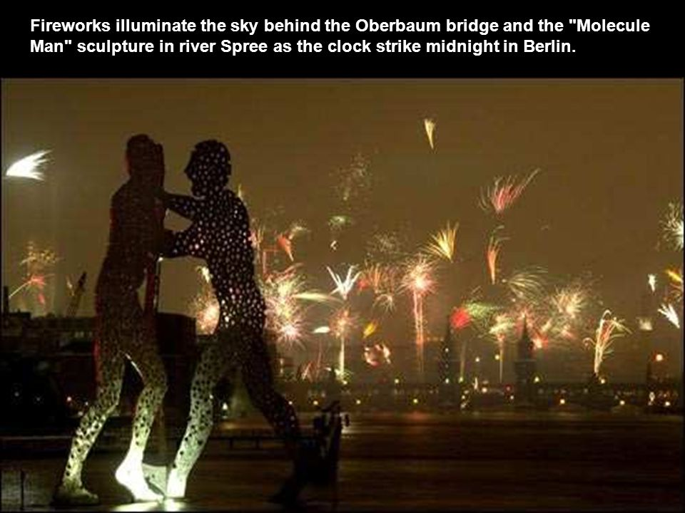 Fireworks illuminate the sky behind the Oberbaum bridge and the Molecule Man sculpture in river Spree as the clock strike midnight in Berlin.